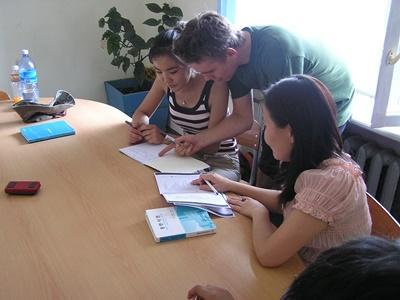 Undervisningsfrivillig assisterer elever med skolearbeid på en skole i Mongolia