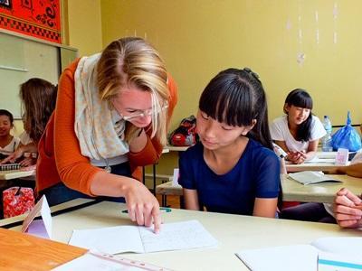 Frivillig på en Undervisningsprosjekt i Mongolia som hjelper en elev med skolearbeid