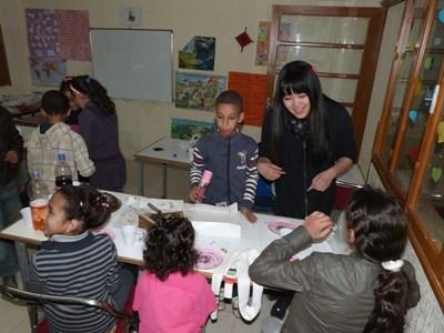 Frivillig gjør håndverk med elever på en skole på undervisningsprosjektet i Marokko