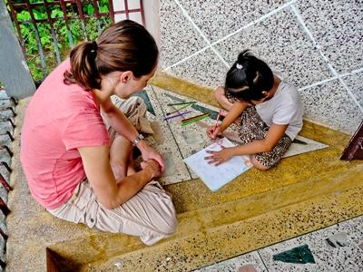 Frivillig lærer gjør håndverk med skolebarn i Nepal, Asia