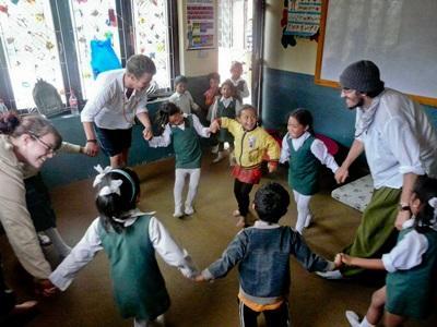 Tre frivillige gjennomfører en time med en gruppe nepalesiske skolebarn
