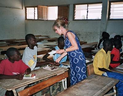 Eldre friviillig underviser en klasse med små barn på en skole i Senegal