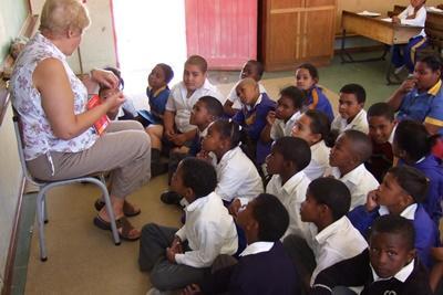 Eldre frivillig underviser en klasse med små barn på en skole i Sør-Afrika