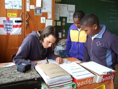 Frivillig på undervisningsprosjektet hjelper elever med skolearbeidet i Sør-Afrika