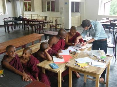 Frivillig underviser en klasse med munker på en skole på Sri Lanka