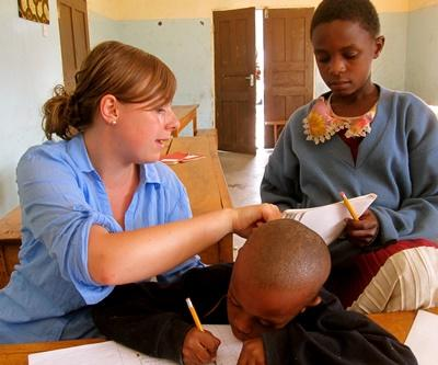 Frivillig lærer retter elevers skolearbeid på en skole i Tanzania