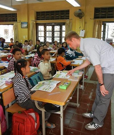 Frivillig hjelper elever med skolearbeid på undervisningsprosjektet i Vietnam