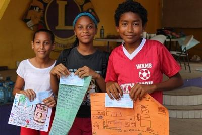 Skolebarn viser fram arbeidene de har gjort sammen med de frivillige i Belize
