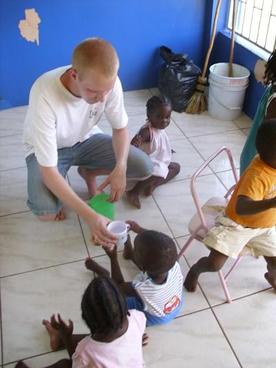 Ungdomsfrivillig på Jamaica gir et barn en kopp med vann