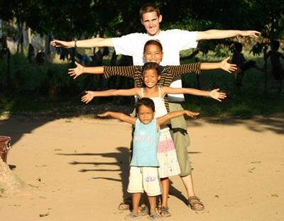 Frivillig  med barn i alle aldre på et omsorgsenter i Kambodsja i skoleferien