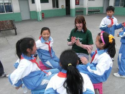 Ungdomsfrivillig leker med jenter på et dyreprosjekt i Kina