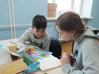 En gutt får undervisning av en frivillig jente i Mongolia