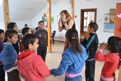En ungdomsfrivillig organiserer en lek for en gruppe barn i Romania