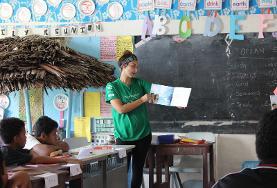 Frivillig leser for en gruppe barn på frivillig arbeid på Samoa