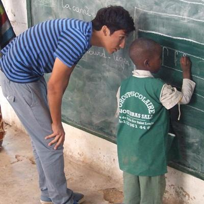 Ungdomsfrivillig hjelper en ung gutt med skolearbeid i Senegal
