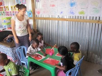 Frivillig hjelper barn med kunst og håndverk på et barneprosjekt i Sør-Afrika
