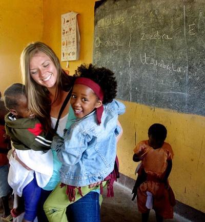 Frivillig holder barn på et omsorgsenter på prosjekt med barn og lokalsamfunn i Tanzania