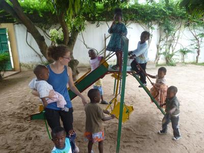 Ungdomsfrivillig leker på lekeplassen med en barneklasse i Togo