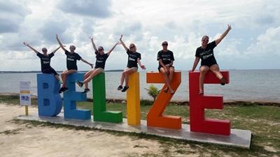 Frivillige på Ungdomsfrivillig sitter på et skilt i Belize.