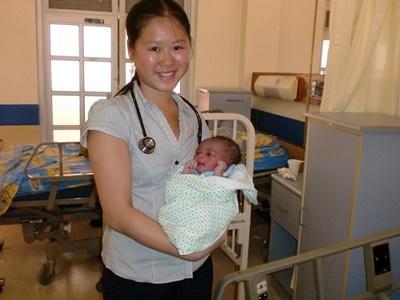 Ungdomsfrivillig som holder en baby på et sykehus på et medisin og helseprosjekt på Jamaica