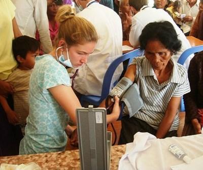 Ungdomsfrivillig sjekker blodtrykket på en eldre dame på et medisinprosjekt i Kambodsja