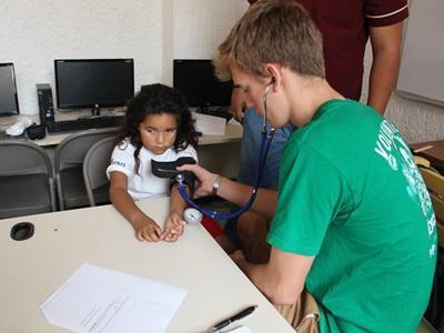 En mannlig frivillig måler blodtrykket til en jente på Folkehelseprosjektet i Mexico