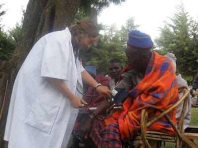 Ungdomsfrivillig som hjelper en eldre dame med funksjonsnedsettelse på et Folkehelseprosjekt i Tanzania