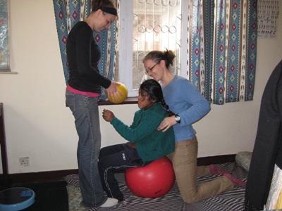 Frivillig og et barn som jobber på treningsballer på et fysioterapiprosjekt i Nepal