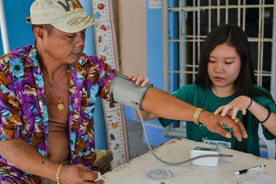 En ungdomsfrivillig måler blodtrykket til en lokal mann under oppsøkende medisinsk arbeid