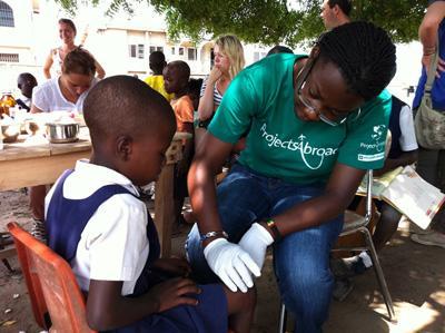 Ungdomsfrivillig som behandler barn på et medisinsk outreachprogram i Ghana