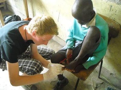 Ungdomsfrivillig behandler et barn på et medisinsk outreachprogram i Kenya