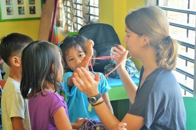 UEn ungdomsfrivillig hjelper en gruppe lokale barn med håndverksaktiviteter