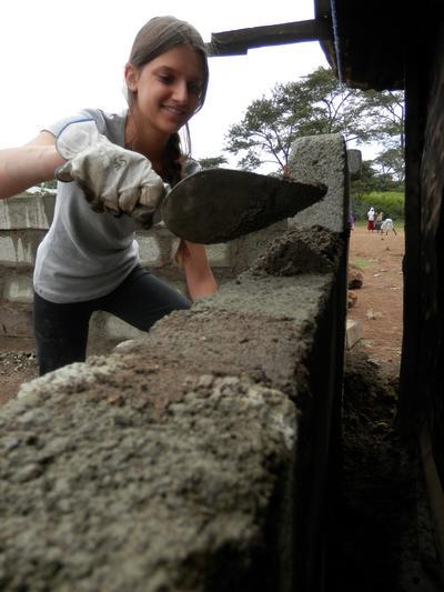 En ungdomsfrivillig murer en vegg på byggeprosjektet i Tanzania