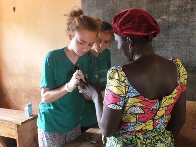 To ungdomsfrivillige måler blodsukkeret til en lokal kvinne på oppsøkende medisinsk arbeid i Togo