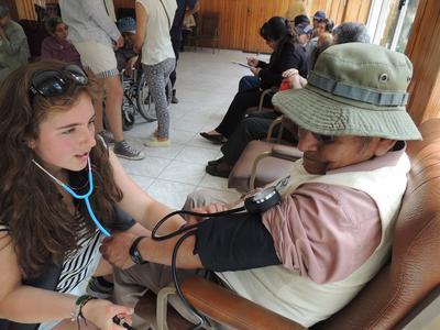 En ungdomsfrivillig måler blodtrykket på en eldre dame under oppsøkende medisinsk arbeid