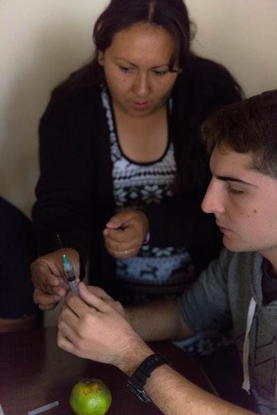 En ungdomsfrivillig lærer hvordan man setter injeksjoner på en workshop