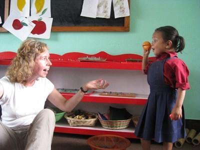 Et barn leker med en Projects Abroad frivillig på skolen hennes i Nepal