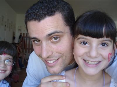 Frivillig som poserer sammen med ansiktsmalt barn på et dagsenter i Europa