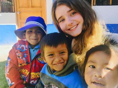 Jente på frivillig arbeid i Sør-Amerika hygger seg med en gruppe barn