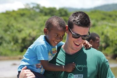 Frivillig holder en ung gutt på et omsorgsenter på barn- og ungdomprosjektet i Stillehavet