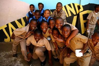 Lokale skolebarn på Jamaica som poserer for fotografen utenfor en prosjektplassering for frivillig arbeid