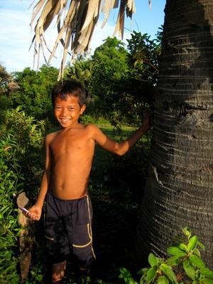 Ung gutt som leker ved et tre på vår plassering i Kambodsja, Asia