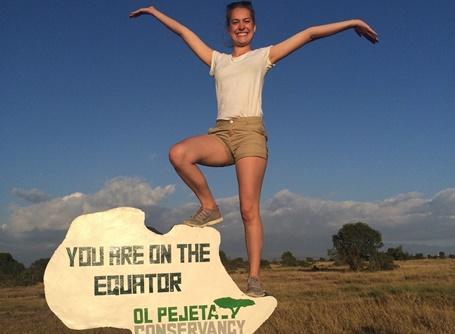 Elise fra Norge poserer på skilt på ekvatorlinjen i Kenya