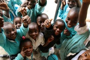 Smilende barn på en barn- og ungdomplassering i Kenya