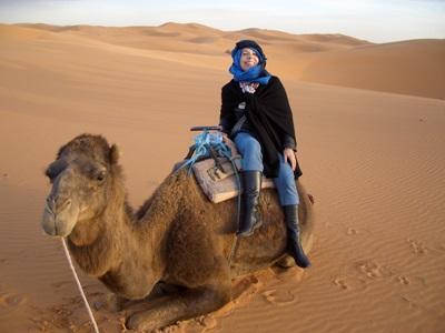 Frivillig som rir kamel i ørkenen under sitt opphold i Marokko