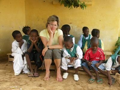 Frivillig sittende på en benk sammen med en gruppe barn i Senegal