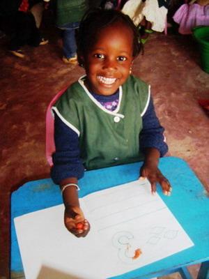 Ung jente som gjør skolearbeid på et frivilligprosjekt i Senegal