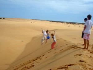 Frivillige i Senegal som hopper fra en sanddyne i ørkenen