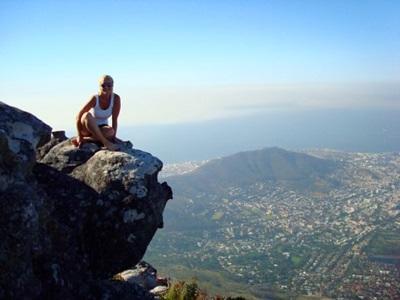 Frivillig som sitter på toppen av Lions Head Mountain under en reise i Sør-Afrika
