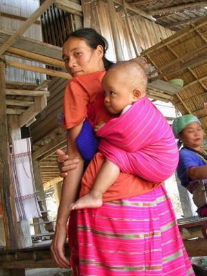 Thaikvinne knytter babyen sin på ryggen på tradisjonell måte